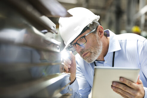 Focused engineer with digital tablet and flashlight examining part in factory - CAIF13158
