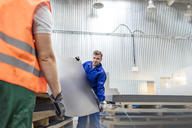 Workers carrying sheet metal in factory - CAIF13161