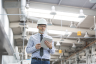 Engineer with hard-hat and digital tablet walking in factory - CAIF13170