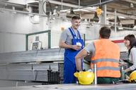 Workers enjoying coffee break in steel factory - CAIF13194
