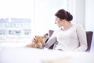 Woman petting dog at window - CAIF13209