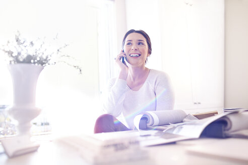 Smiling interior designer talking on cell phone in bright office - CAIF13212