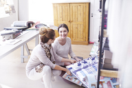 Interior designers browsing fabric swatches in office - CAIF13218