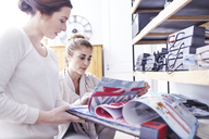 Interior designers browsing fabric swatches in office - CAIF13221