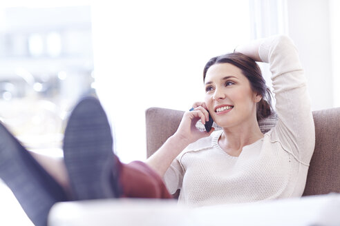 Smiling woman talking on cell phone with feet up on sofa - CAIF13224