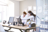 Businesswomen talking at computer in office - CAIF13236
