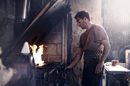 Blacksmith working at fire in forge - CAIF13242