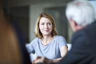 Businesswoman listening to businessman in meeting - CAIF13269