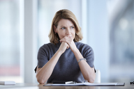 Pensive businesswoman looking away in conference room - CAIF13281