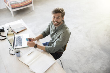 Portrait of young man sitting at desk with mobile phone and laptop - CAIF13287
