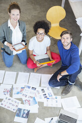 Portrait of three young people sitting on floor and working together - CAIF13293