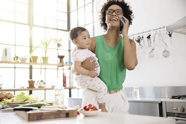 Mother holding her baby daughter while using mobile phone in kitchen - CAIF13296