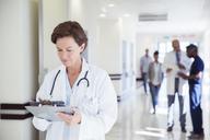 Doctor using digital tablet in hospital corridor - CAIF13329