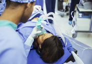 Anesthesiologist holding oxygen mask over patient's face in operating room - CAIF13344