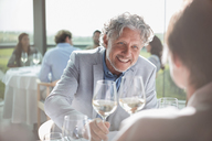 Smiling couple drinking wine in sunny restaurant - CAIF13353
