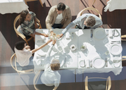 Overhead view friends toasting wine glasses at sunny restaurant table - CAIF13380