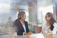 Businesswomen talking in sunny conference room - CAIF13386