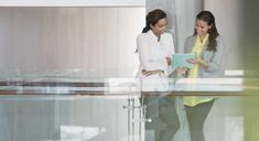 Businesswomen reviewing paperwork in office corridor - CAIF13392