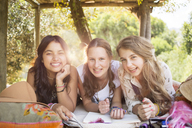 Three teenage girls having fun in tree house in summer - CAIF13407