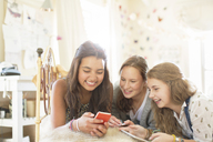 Three teenage girls using smartphone together while lying on bed in bedroom - CAIF13422