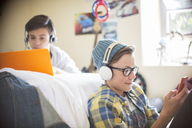 Two teenage boys using electronic devices in room - CAIF13449