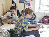 Two teenage boys using digital devices in room - CAIF13458