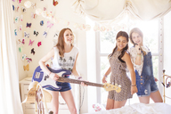 Three teenage girls playing music and singing in bedroom - CAIF13461