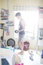 Teenage boy exercising with dumb bell in his room - CAIF13470