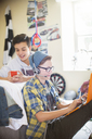 Two teenage boys using electronic devices in room - CAIF13476