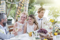 Young couple and their guests sitting at table during wedding reception in garden - CAIF13485