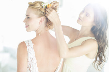 Bridesmaid helping bride with hairstyle in garden - CAIF13491
