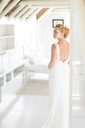 Young bride standing in sunny bedroom - CAIF13494