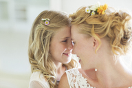 Bride and bridesmaid facing each other smiling - CAIF13497
