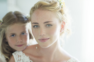 Portrait of bride and bridesmaid looking at camera - CAIF13503