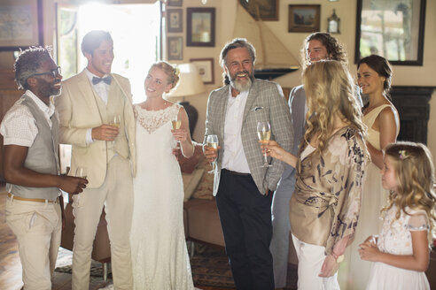Young couple with guests and champagne flutes at wedding reception - CAIF13527