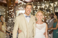 Portrait of smiling young couple standing in falling confetti during wedding reception - CAIF13536