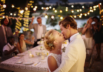 Young couple kissing during wedding reception in domestic garden - CAIF13551