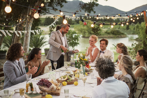 Best man pouring champagne into flutes during wedding reception in domestic garden - CAIF13554