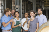 Winery employees tasting white wine in cellar - CAIF13626