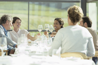 Friends toasting wine glasses in sunny restaurant - CAIF13635