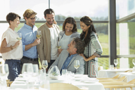 Friends drinking wine in winery dining room - CAIF13650