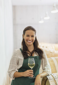 Portrait confident vintner with white wine in cellar - CAIF13674