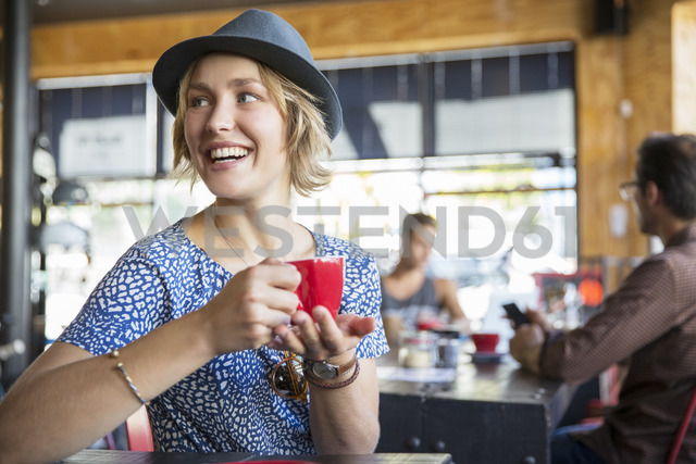 Smiling woman drinking coffee looking over shoulder in cafe - CAIF13710