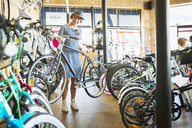 Woman selecting bicycle from rack in bicycle shop - CAIF13713