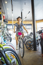 Smiling woman riding bicycle in bike shop - CAIF13716