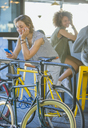 Smiling woman leaning on railing texting with cell phone above bicycle - CAIF13719