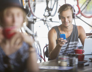 Young man with headphones and laptop texting with cell phone in cafe - CAIF13725