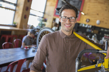 Portrait smiling man with eyeglasses carrying bicycle in cafe - CAIF13737