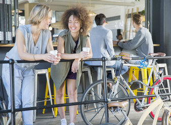 Smiling friends hanging out drinking coffee at cafe patio railing near bicycles - CAIF13752