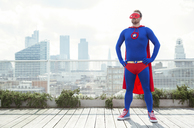 Superhero standing with hands on hips on city rooftop - CAIF13758